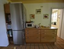 Küche in Buche mit glatter Front, freistehender Kühlschrank, Eckregal