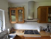 Landhausküche mit Hängeschränken in Pinie und Dunstabzug in Edelstahl