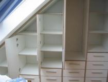 Dachschrägenschrank in MDF-weiß foliert mit Türen und Vollauszugschubladen im geöffneten Zustand