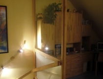 Treppenhausabschluß zum Dachboden in Buche mit Glasscheiben und Schiebetür - Frontansicht ins Treppenhaus