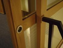 Treppenhausabschluß zum Dachboden in Buche mit Glasscheiben und Schiebetür - Detailaufnahme Abschluß Treppengeländer zum Seitenteil, Tür im geöffnetem Zustand