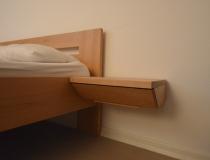 Schlafzimmer: Bettdetail in Buche, Nachttischablage mit Schublade